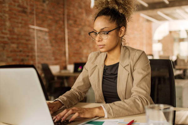 Woman working on laptop at office desk