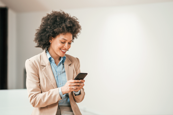 Woman in business suit on smartphone indoors