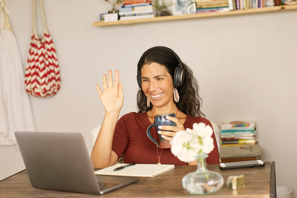 Woman waving to laptop screen in virtual meeting